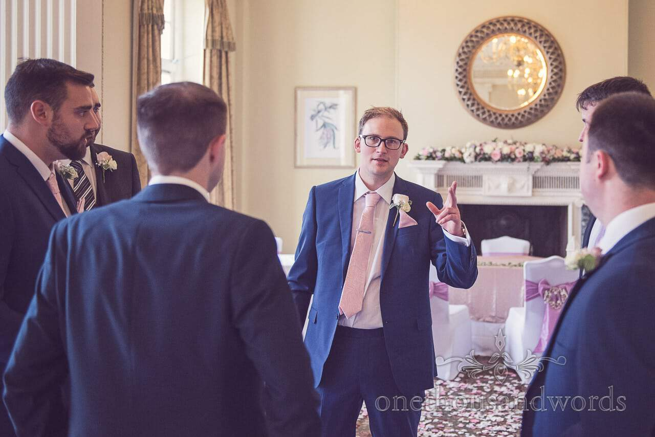 Groom in blue suit and pink tie in ceremony room at Northcote House wedding