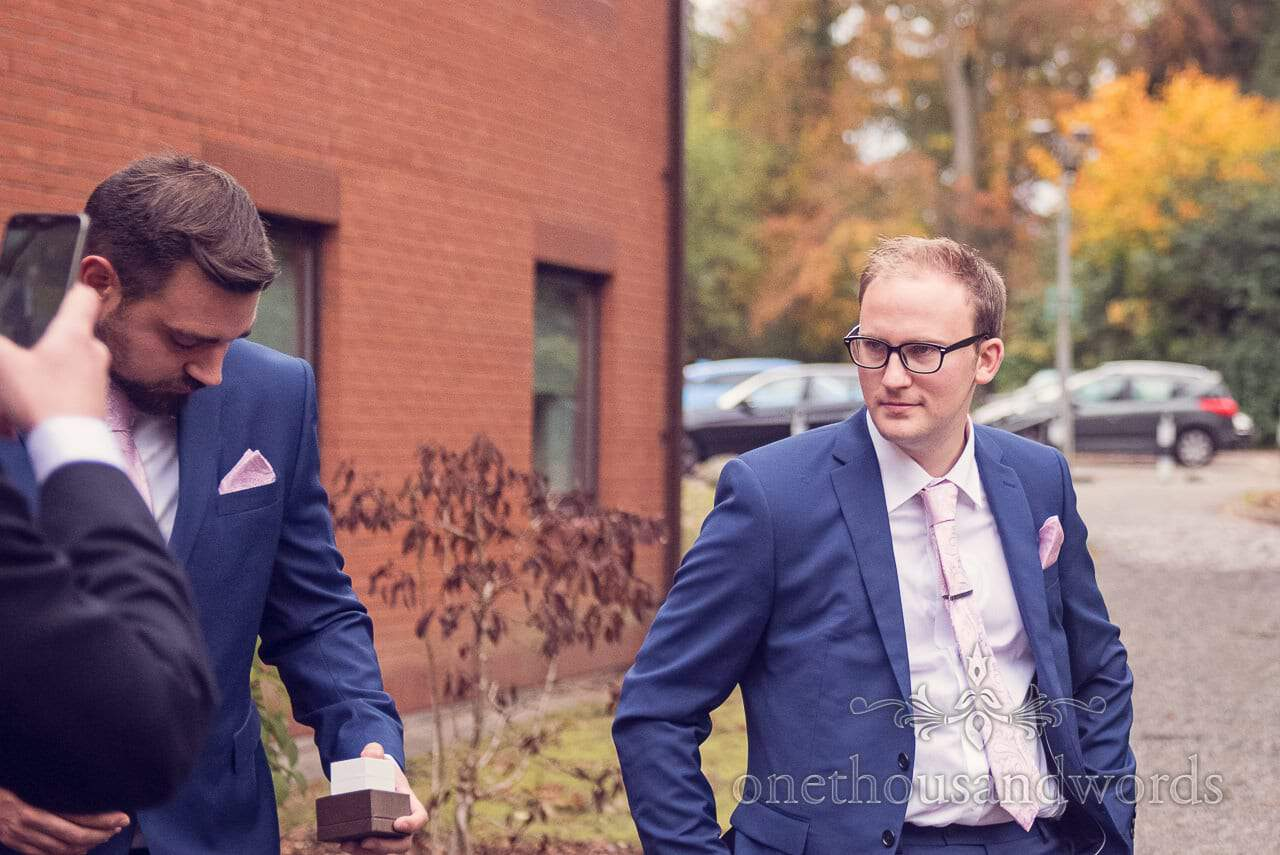 Groom in blue wedding suit with pink tie posing for the groommen at Northcote House wedding