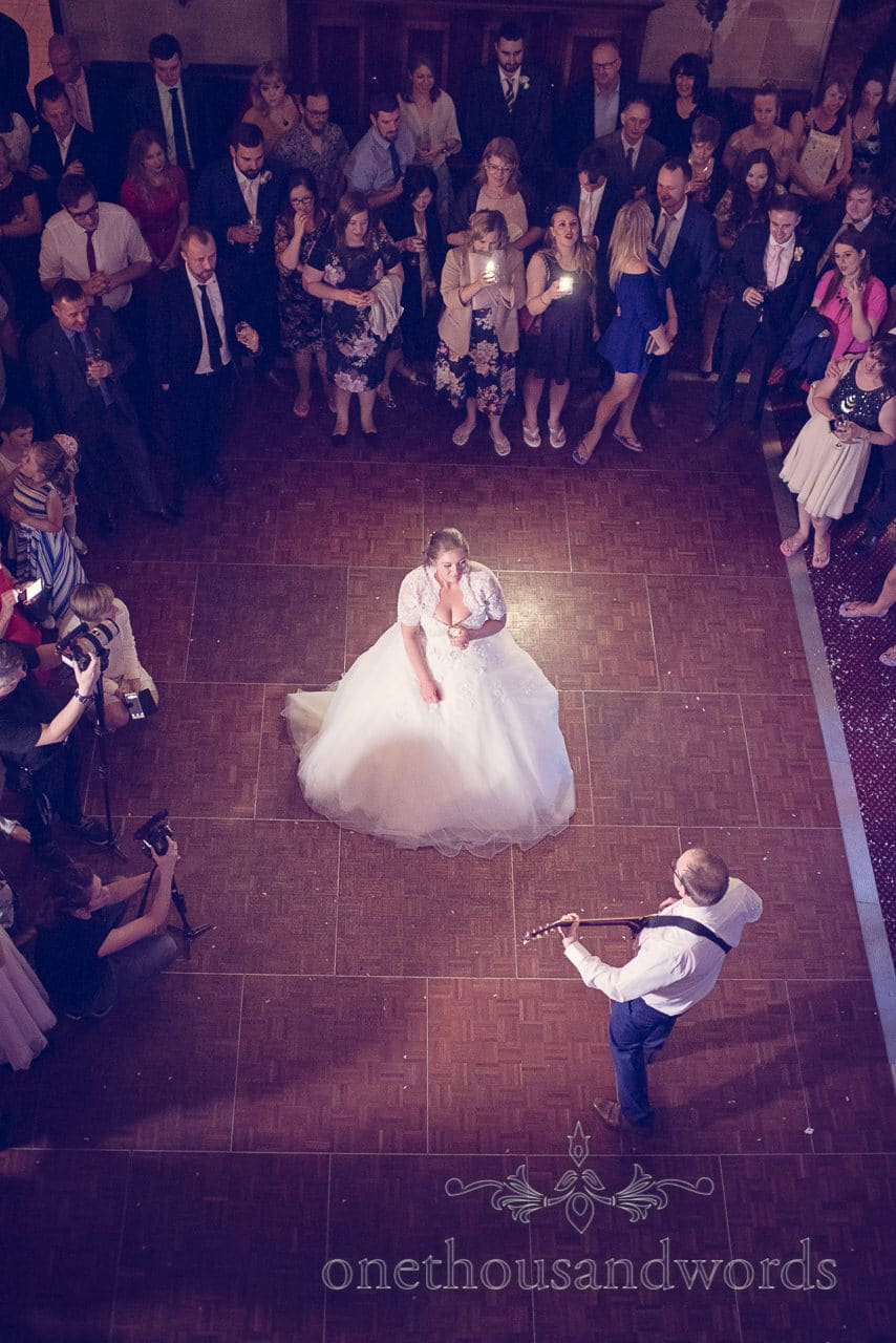 Groom plays guitar to bride during the first dance at Northcote House wedding