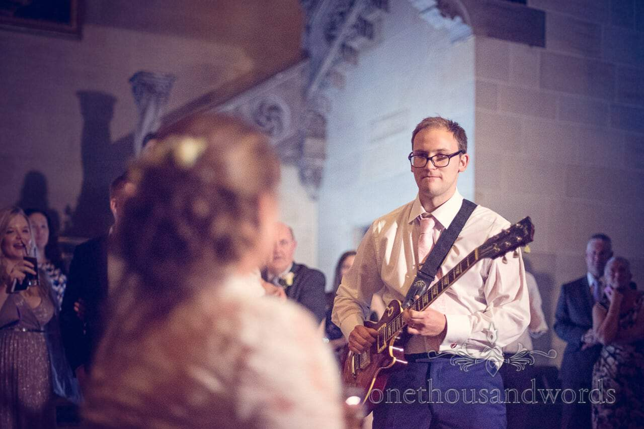 Groom serenades bride with electric guitar during first dance at Northcote House wedding