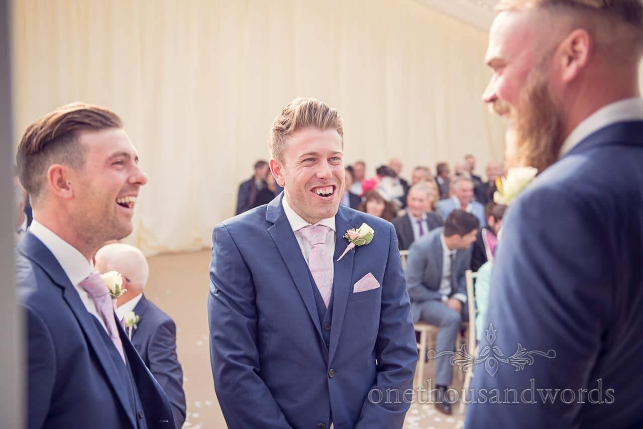 Groom shares joke with groomsmen at Holme for Gardens Dorset wedding