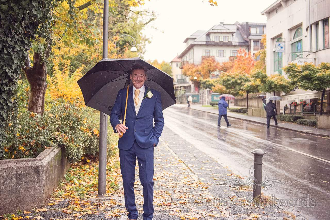 Groom smiles in blue Ted Baker suit and gold tie under umbrealla in autumn rain in Bled