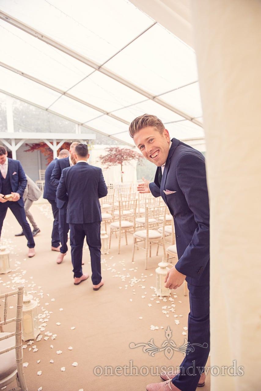 Groom supervises groomsmen at Holme for Gardens Dorset wedding