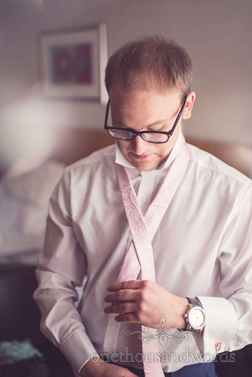 Groom with pink paisley patterned wedding tie on wedding morning at Northcote House