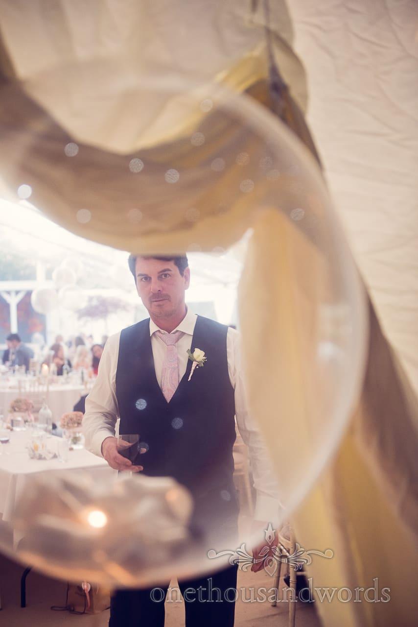 Groomsman through a balloon at Holme Gardens Dorset Wedding