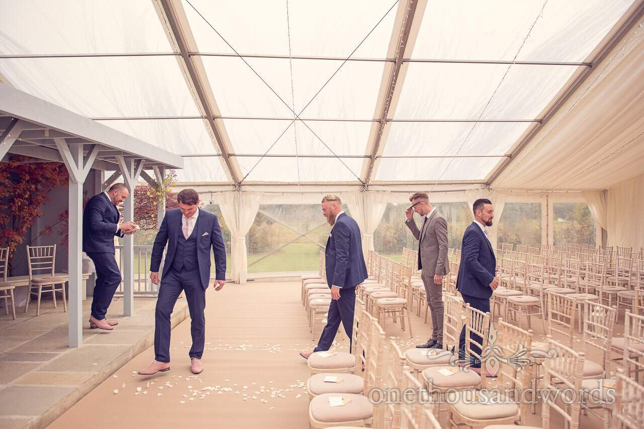 Groomsmen arrange flower petals at Holme for Gardens Dorset wedding