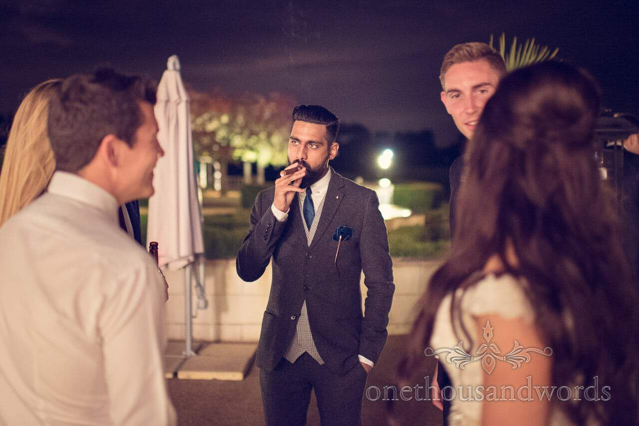 Guest smokes cigar at Froyle Park wedding photographs