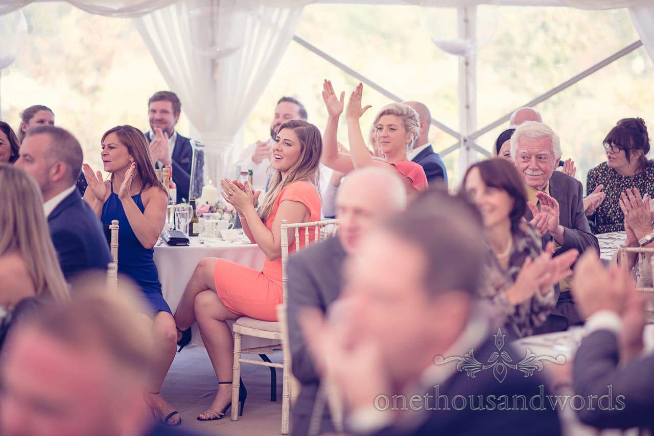 Guests applaud father of the bride at Holme for Gardens Dorset wedding