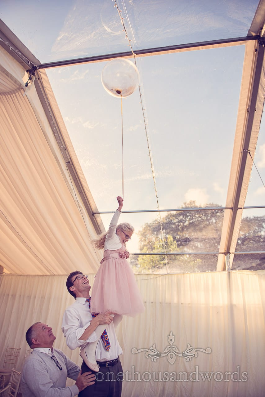 Guests help flower girl capture balloon at Holme for Gardens Dorset wedding