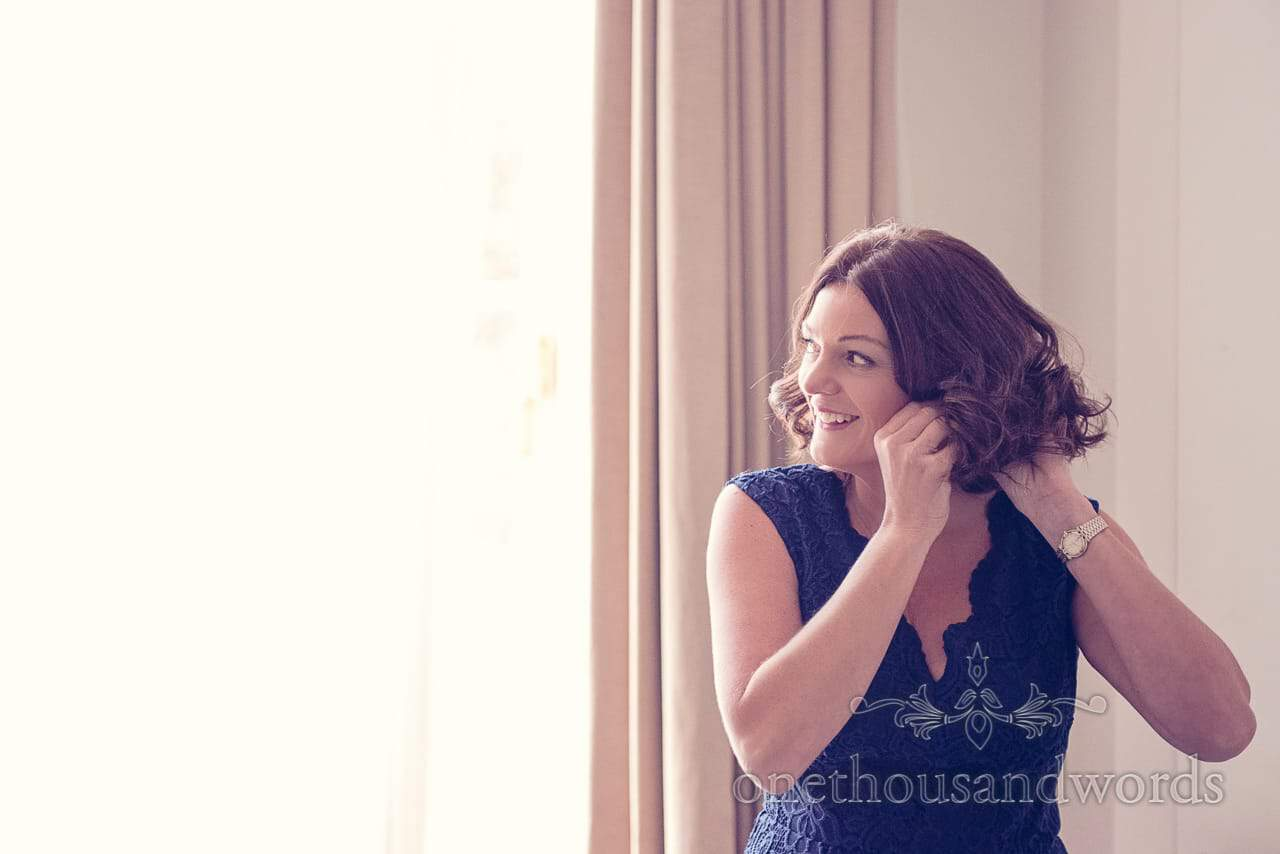 Mother of the bride in dark blue dress portrait photograph adjusts ear rings during bridal preparation