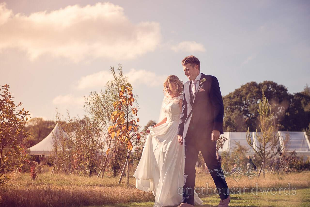 Newlyweds with marquee at Holme for Gardens Dorset wedding
