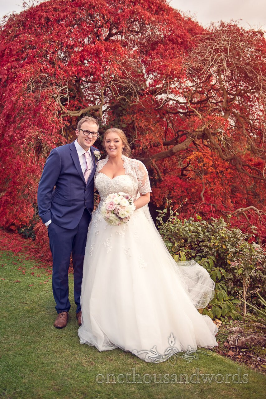 Northcote House wedding photograph of bride and groom with red acer in autumn