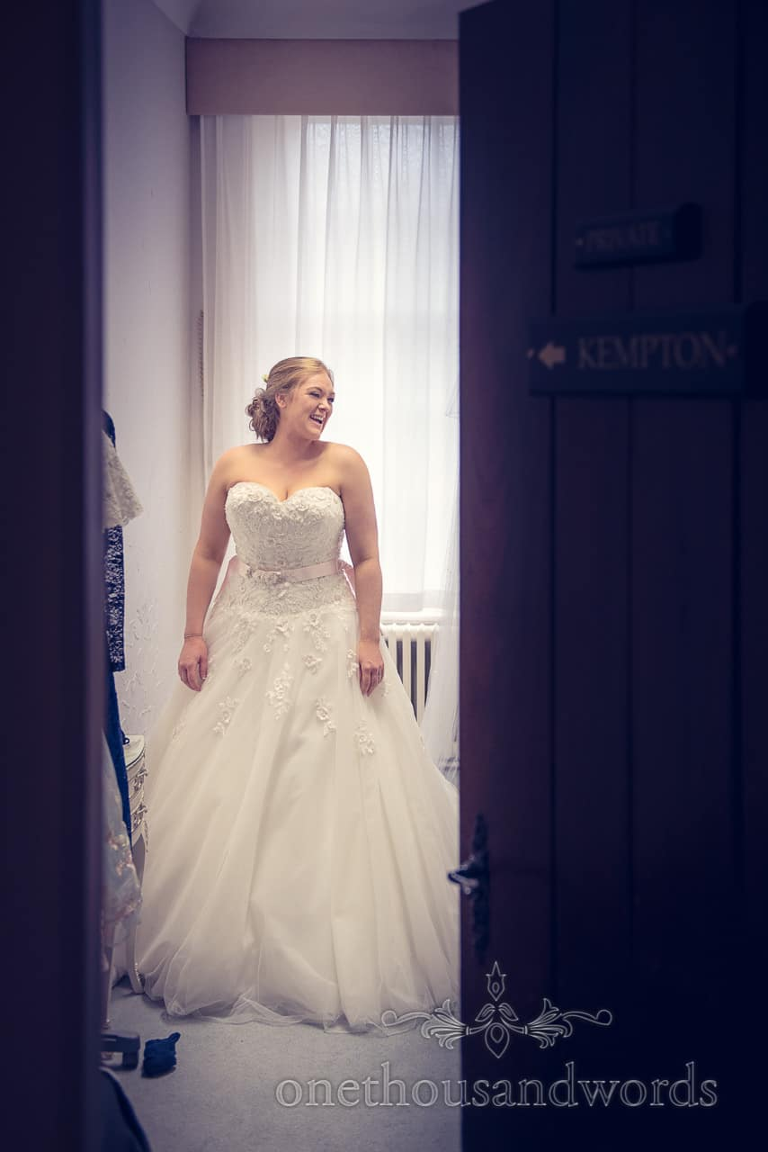 Northcote House wedding photographs of bride putting on wedding dress and laughing