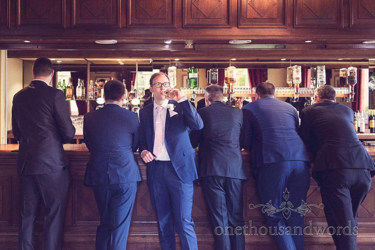 Northcote House Wedding Photographs of groom and groomsmen at bar in morning