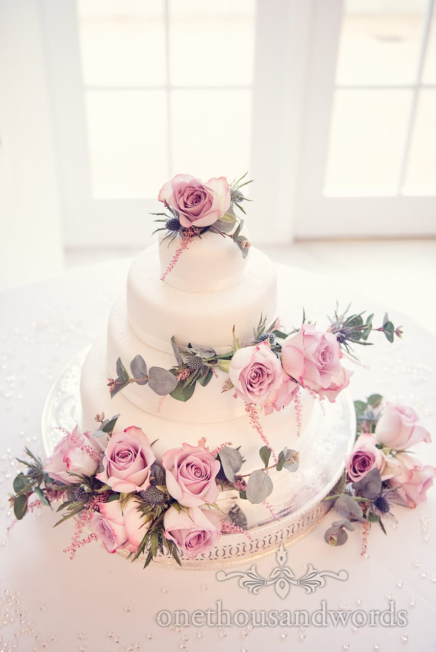 Wedding cake decorated with pink roses and thistles