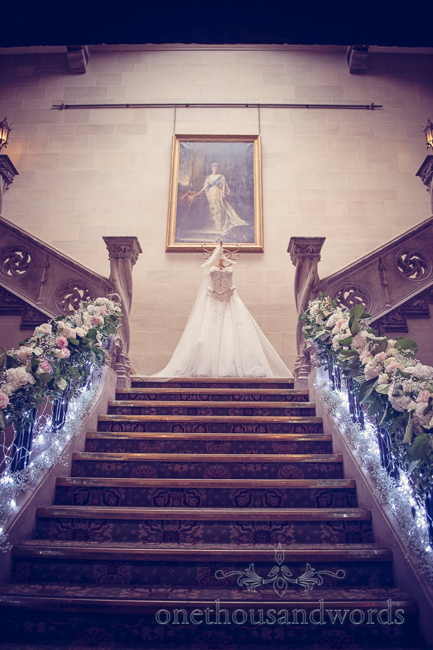 Wedding dress on grand stone stair case with wedding flowers at Northcote House wedding