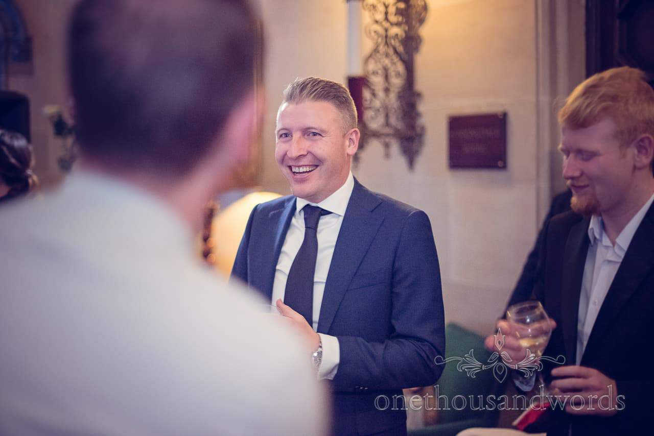 Wedding guest in blue suit laughing at Northcote House evening reception