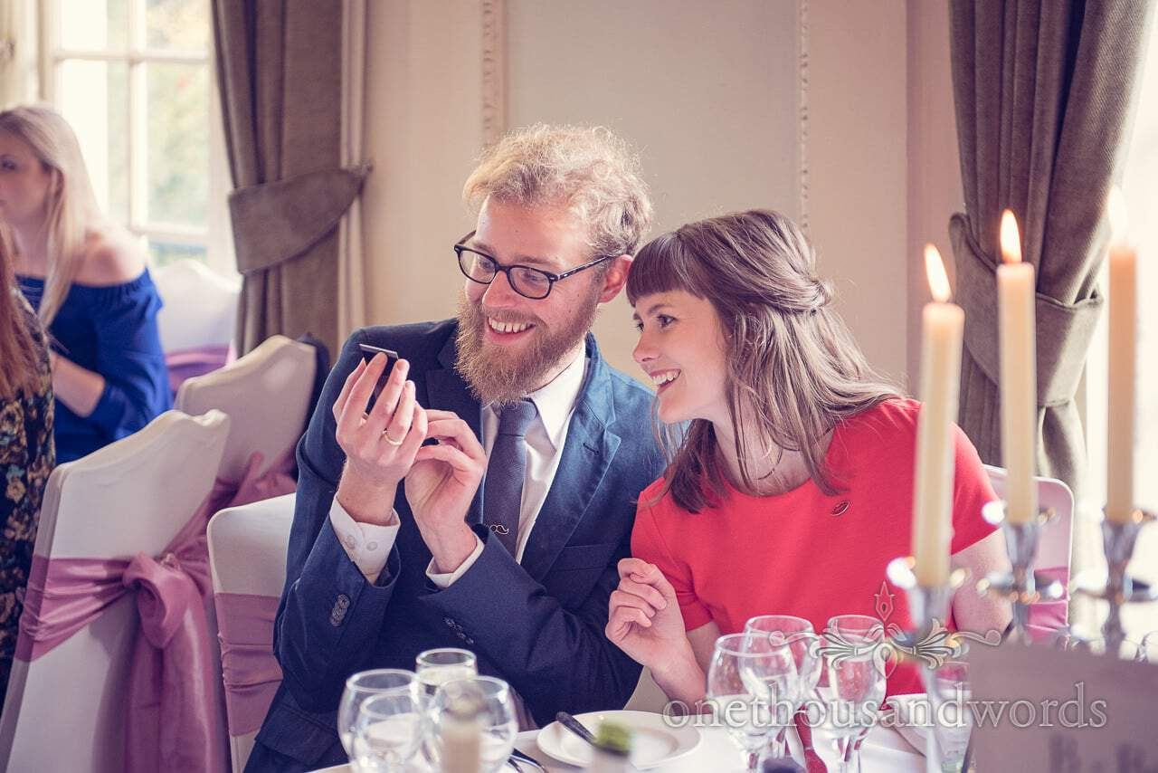 Wedding guests laughing at facetime conversation at Northcote House wedding