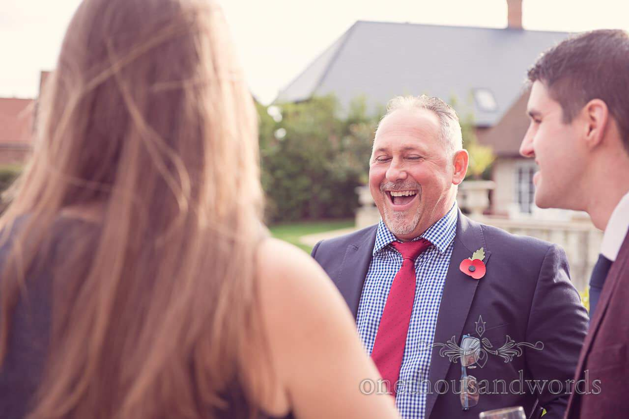 Wedding guests share a joke in garden