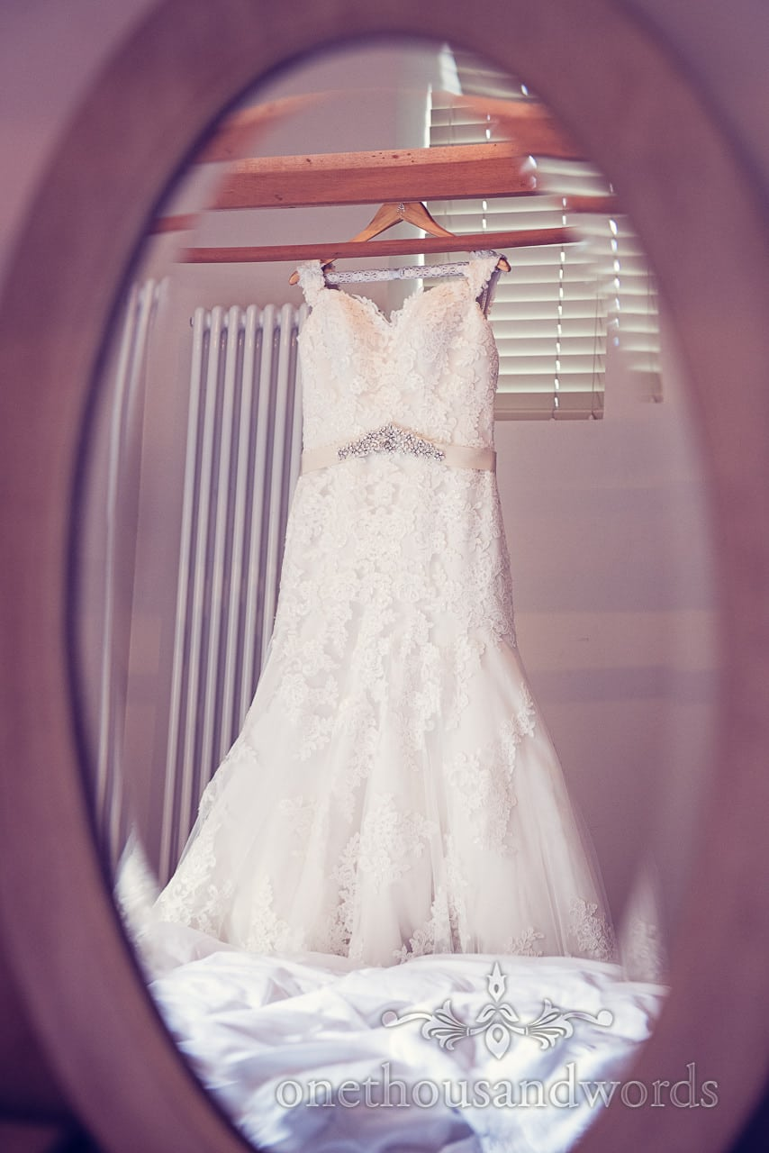 White weddign dress with detailed applique and diamante belt hangs in mirror