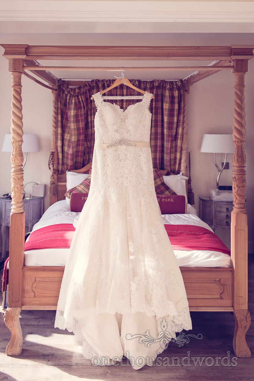 White wedding dress hanging on four poster bed at Froyle Park wedding venue
