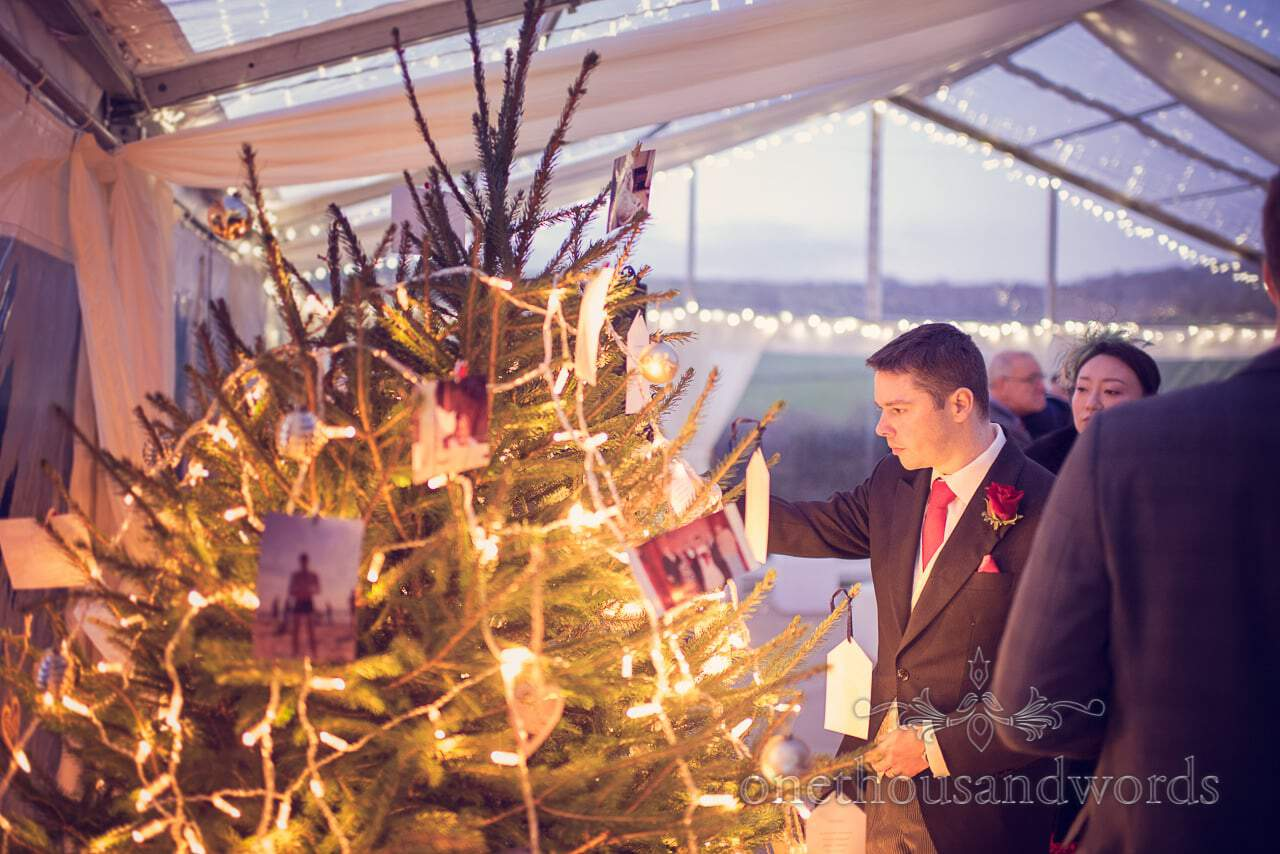 Best man inspects Christmas tree during wedding reception at Plush manor