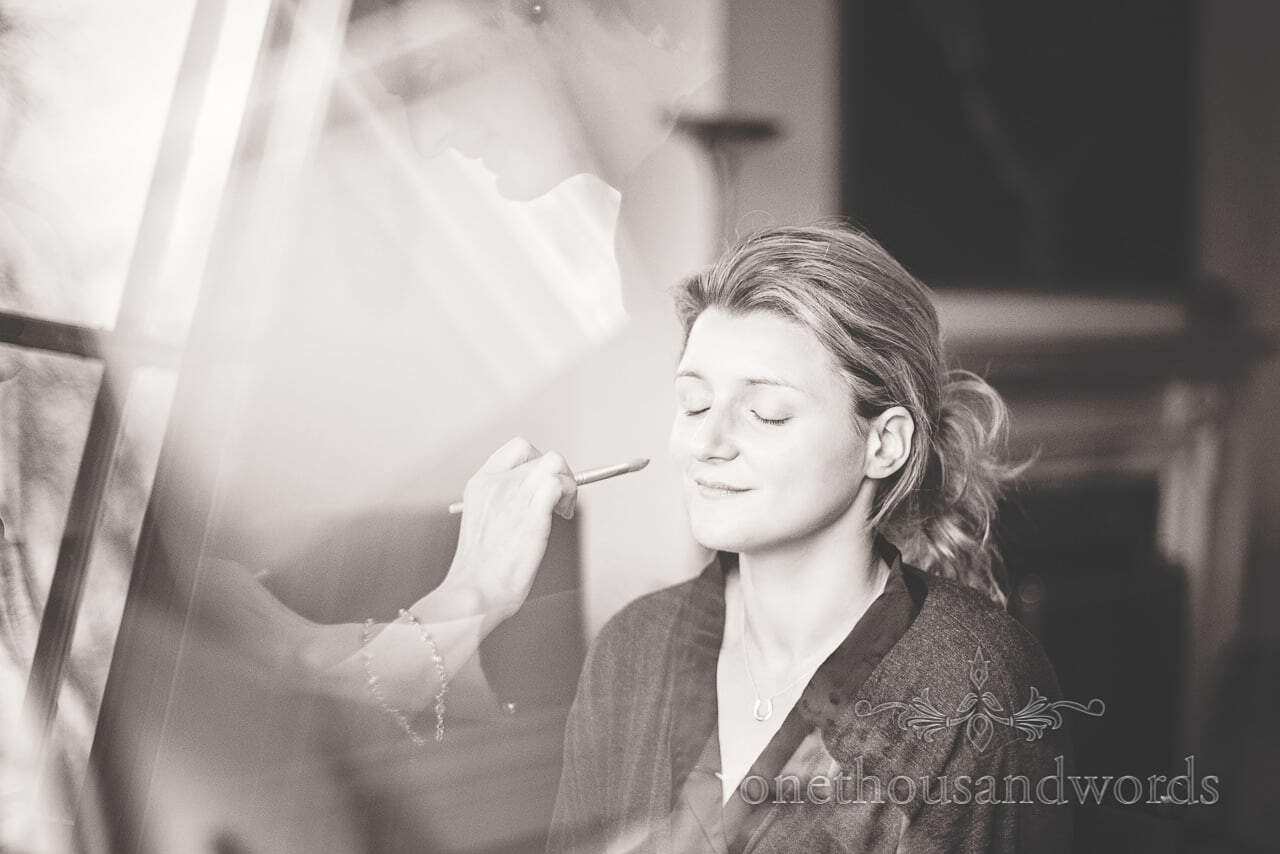 Black and white photograph of bride having wedding makeup styled at plush manor