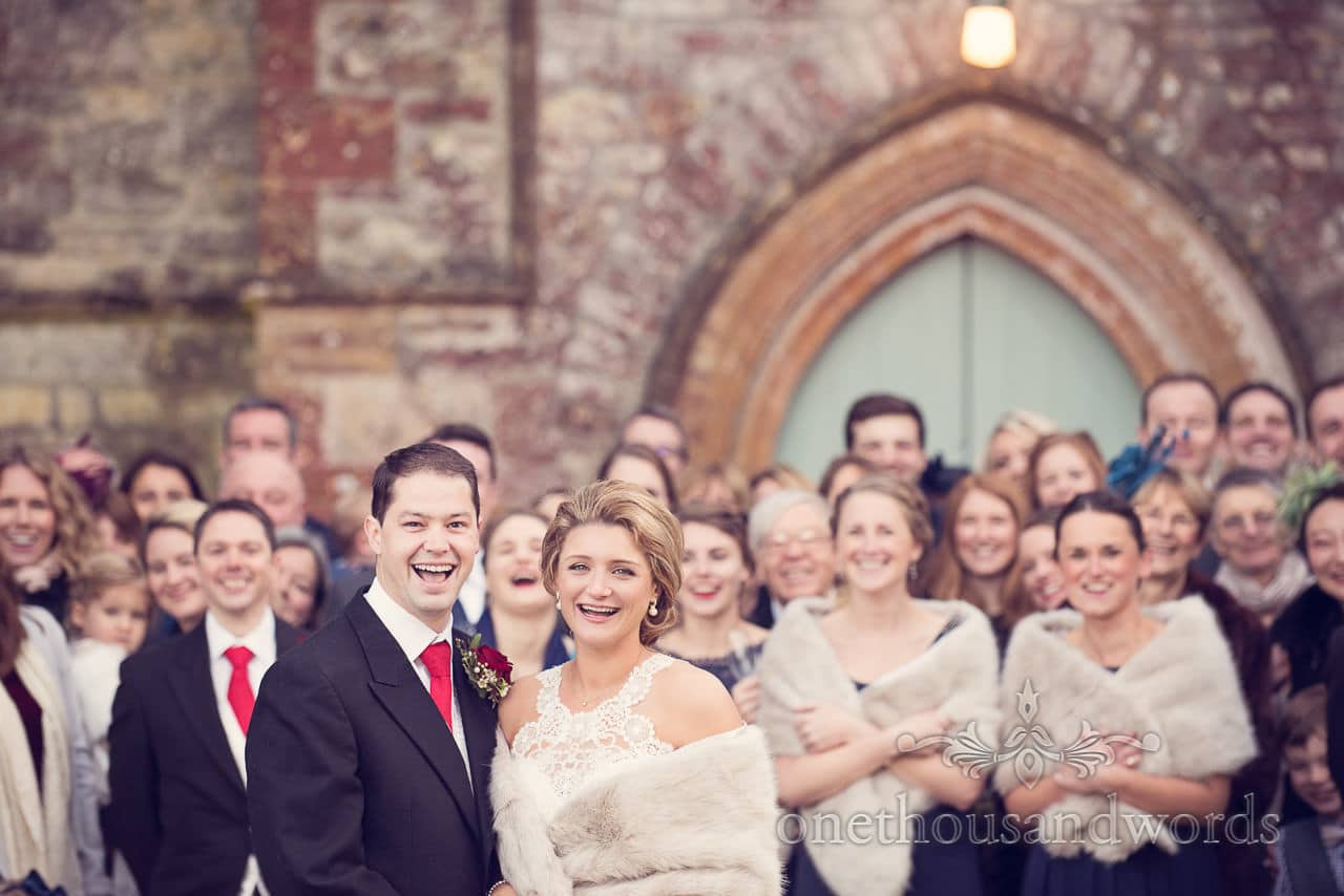 Bride and groom in front of guests during group photograph at Plush manor