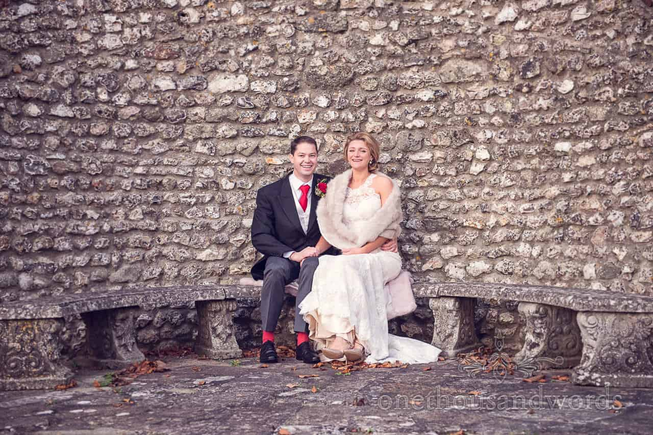 Bride and groom seated against stone wall at Plush manor wedding photographs