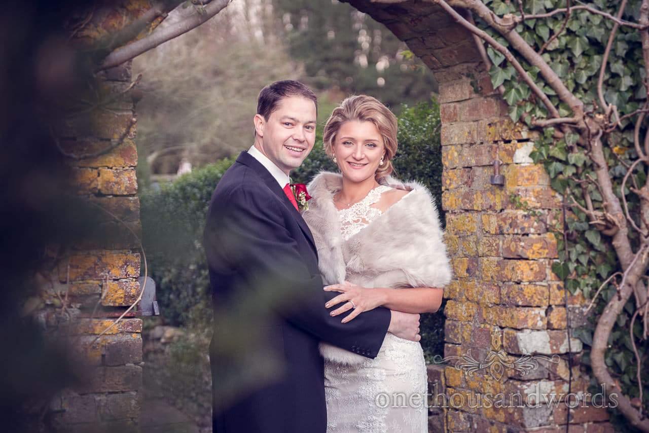 Bride and groom under archway in Plush manor wedding venue gardens