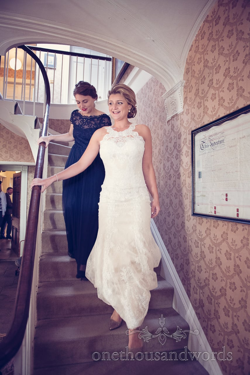 Bride descends the stairs on morning of Plush manor wedding photographs