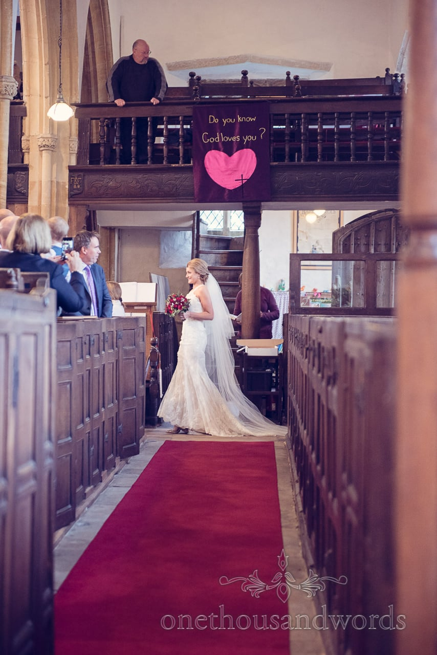 Bride enters St Mary's Church wedding under pink love heart in Puddletown