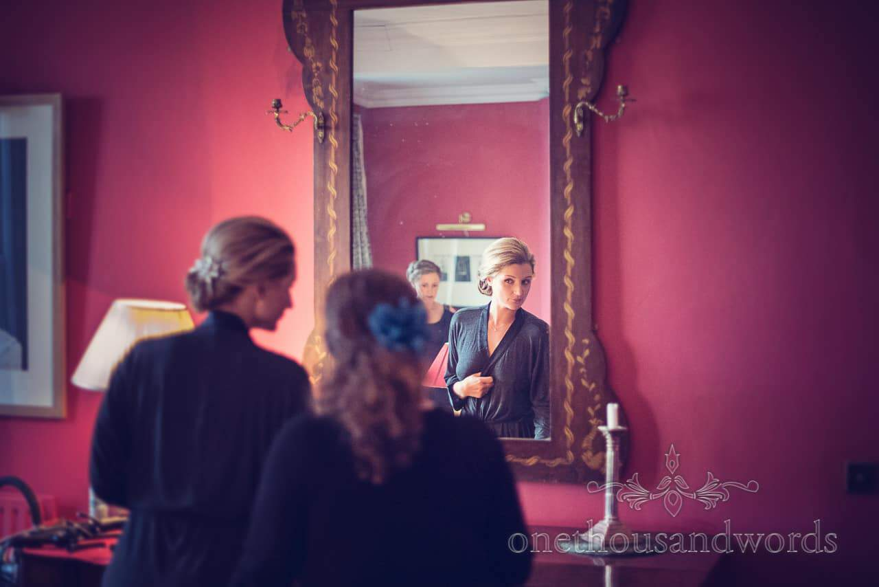 Bride in the mirror on morning of Plush manor wedding photographs