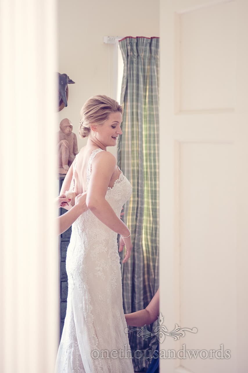 Bride is helped into her wedding dress at Plush manor wedding photographs