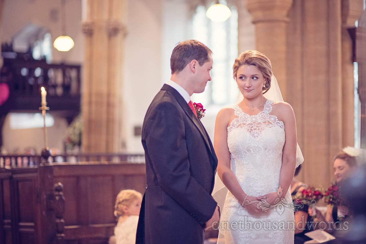 Bride looks at groom during wedding ceremony at St Mary's Church wedding in Puddletown