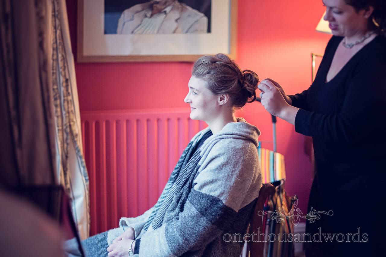 Bridesmaid has wedding hair styled on morning of Plush manor wedding photographs