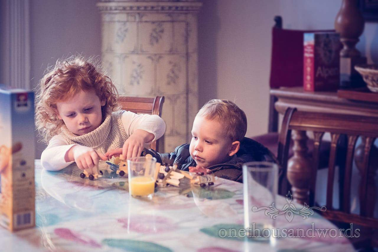 Children paly with toy train on morning of Plush manor wedding photographs