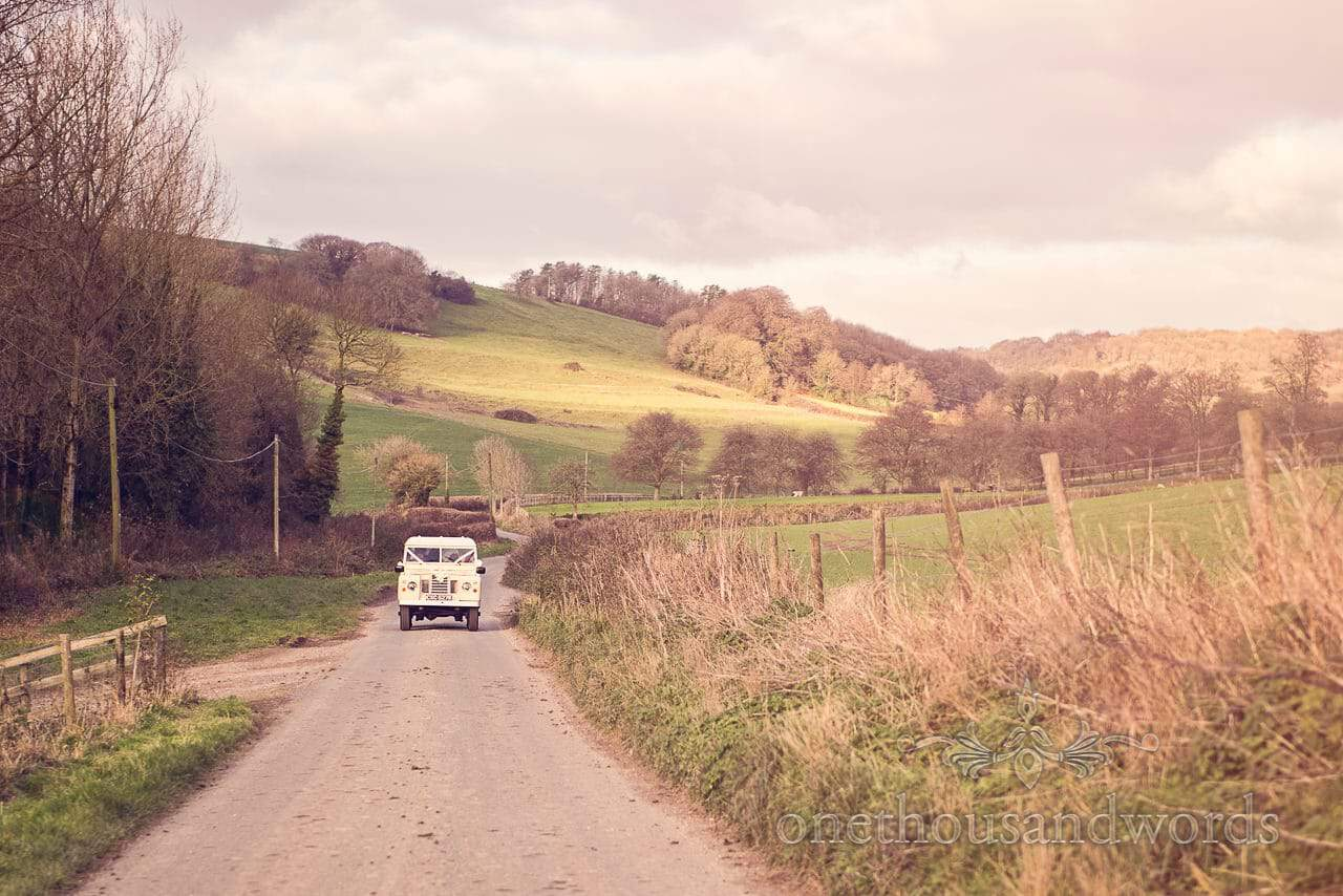 Classic wedding Land Rover carries bridal party through Dorset Countryside to wedding