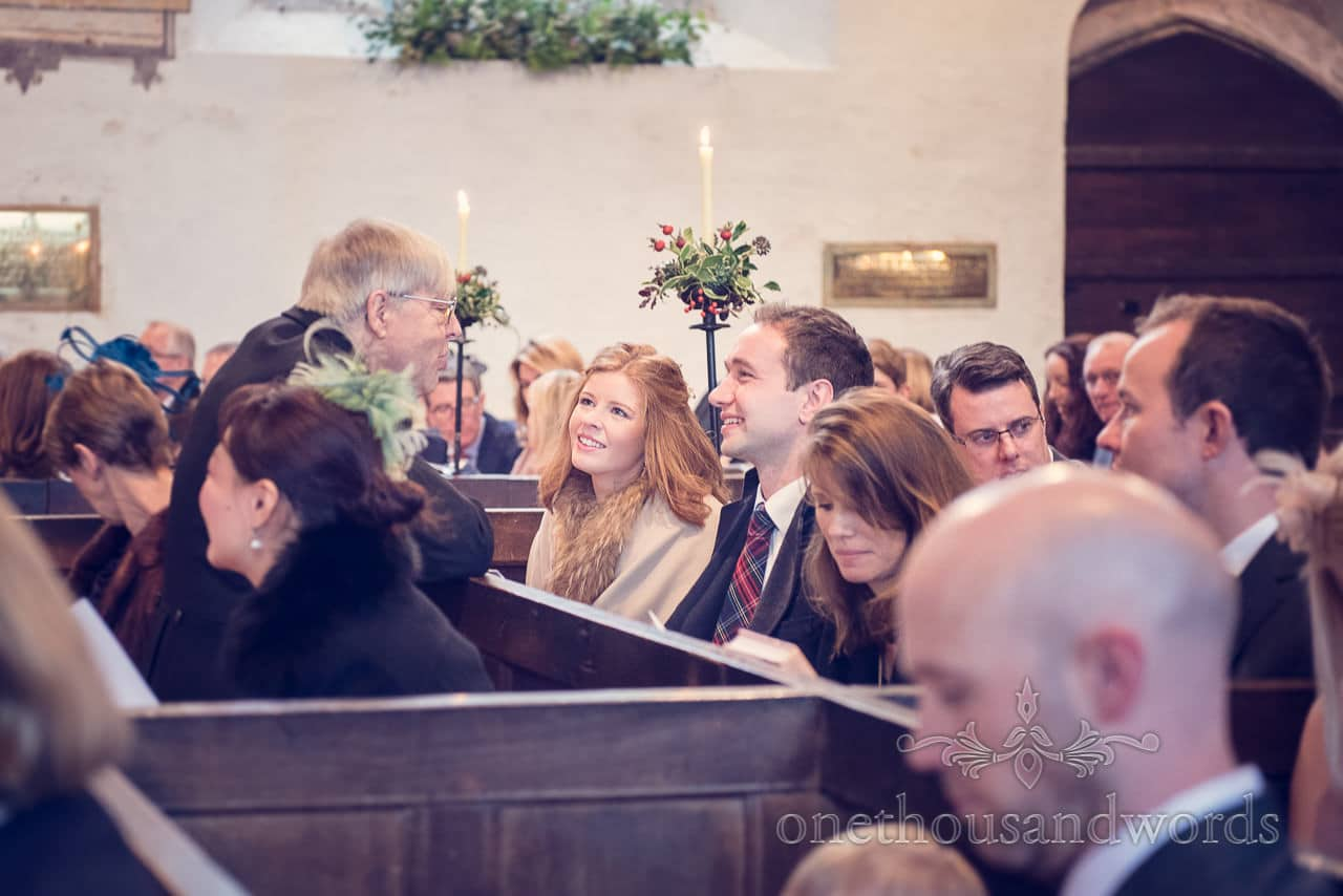 Father of the groom chats to guests in church from Plush manor wedding photographs