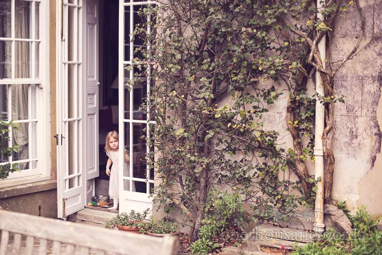 Flower girl in house doorway on morning of Plush manor wedding photographs