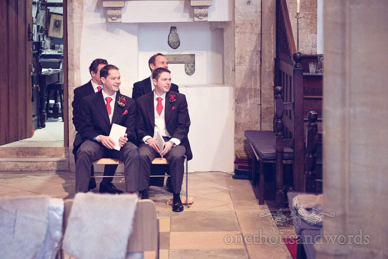 Groom and groomsmen await the arrival of the bride in Dorset stone church