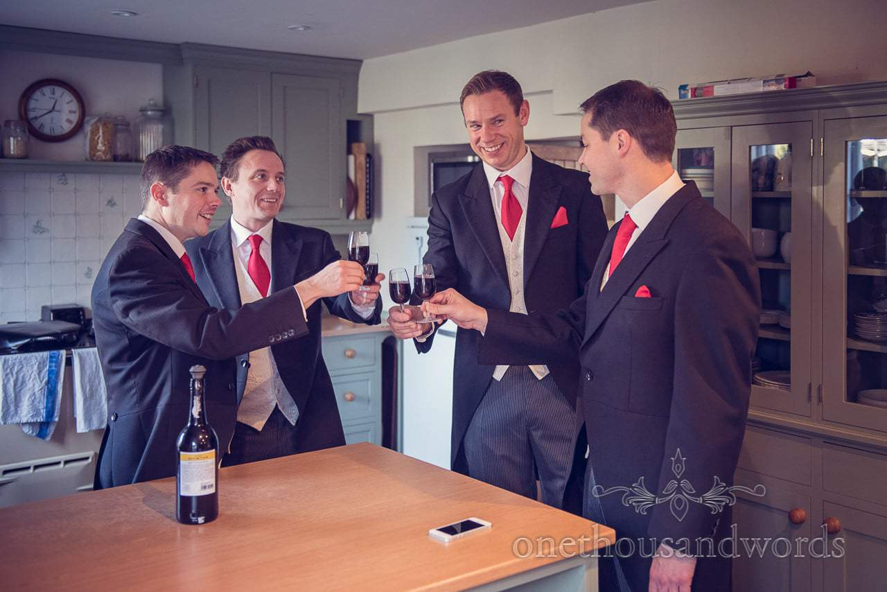 Groom and groomsmen drink a toast during Plush manor wedding preparations