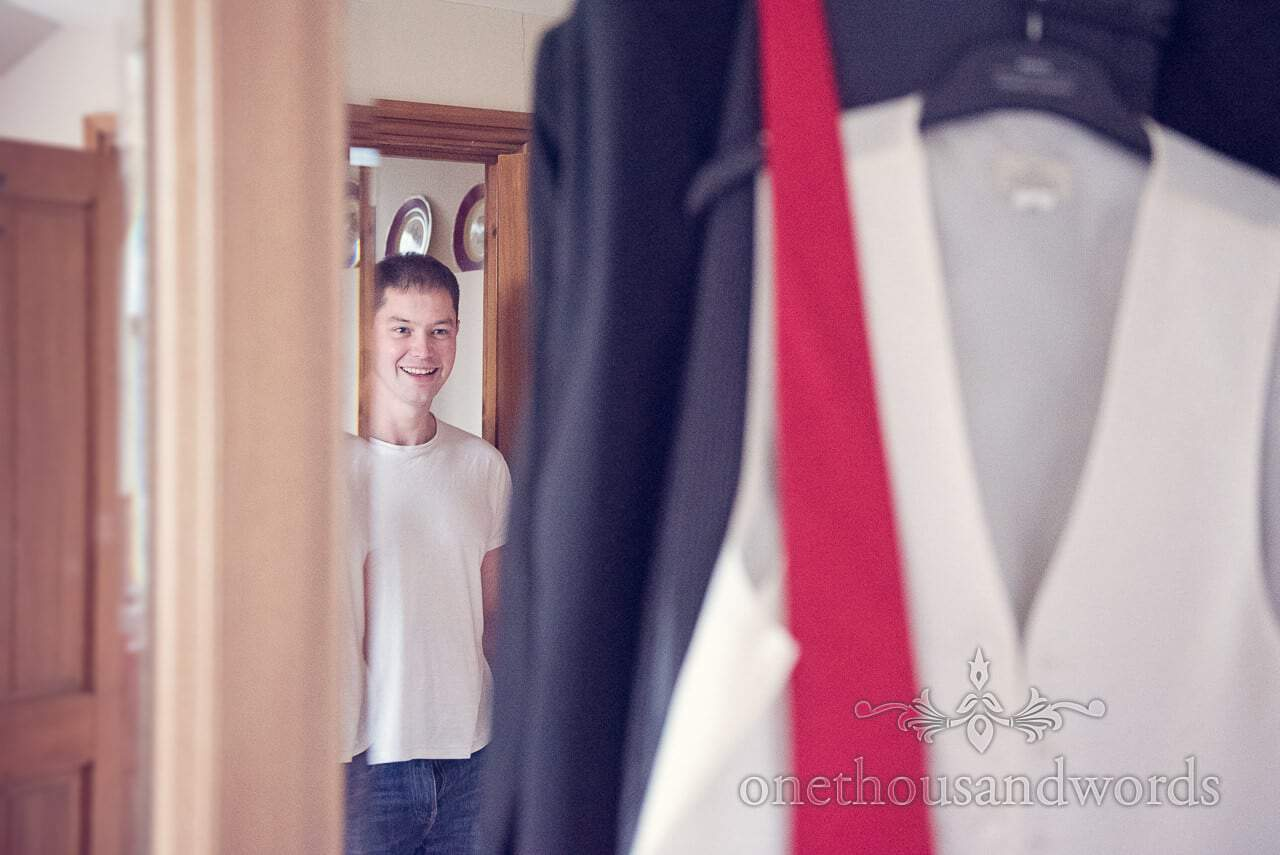 Groom in the mirror before Plush manor wedding photographs