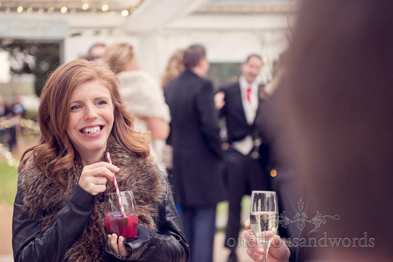 Guest enjoys drink at reception from Plush manor wedding photographs