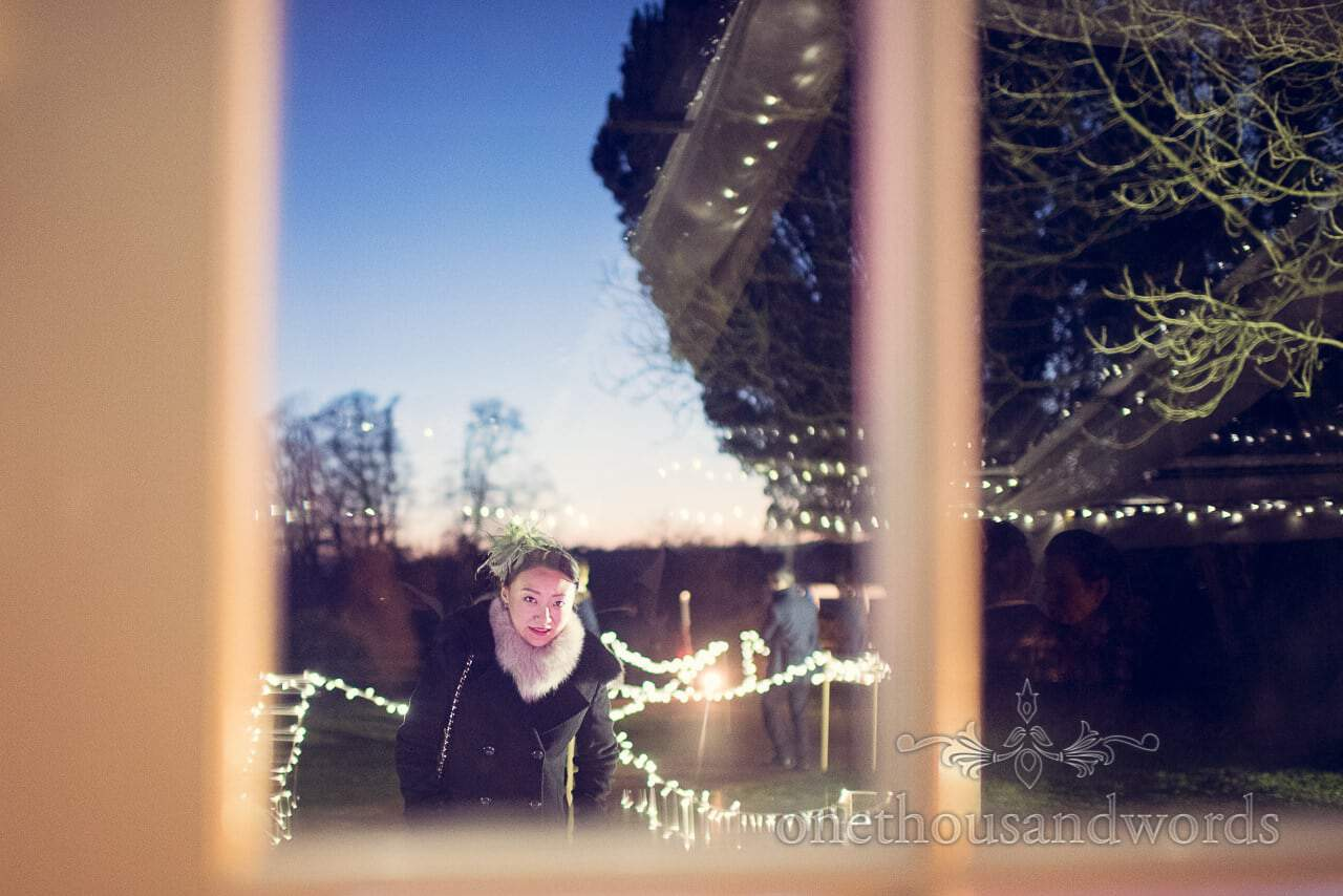 Guest portrait with sunset through marquee door at Plush Manor wedding