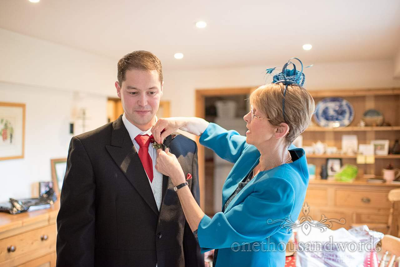 Mother helps groom with buttonhole from Plush manor wedding photographs