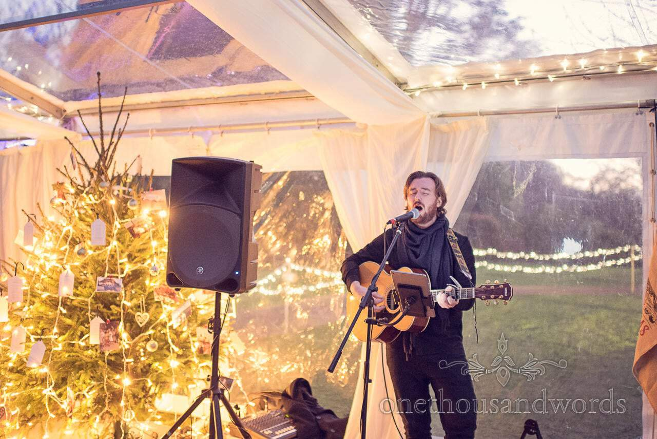 Musician plays guitar next to christmas tree during drinks reception at Plush manor