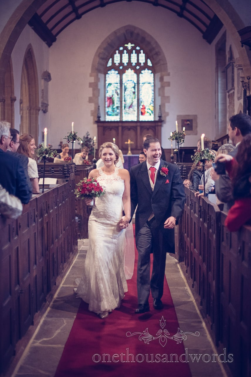 Newlyweds walk down the aisle at St Mary's Church wedding in Puddletown