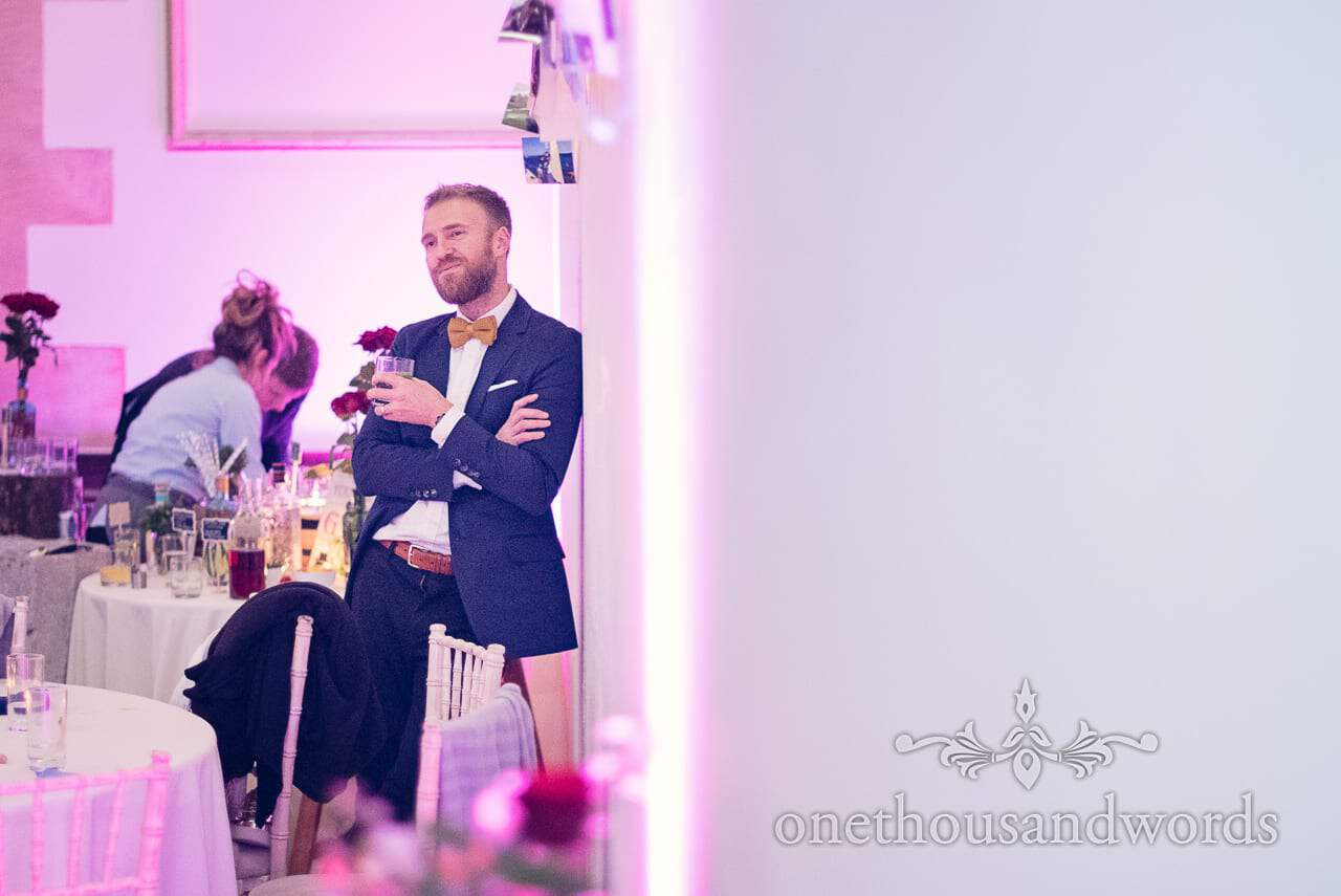 Wedding guest in blue suit and bow tie at plush manor wedding evening