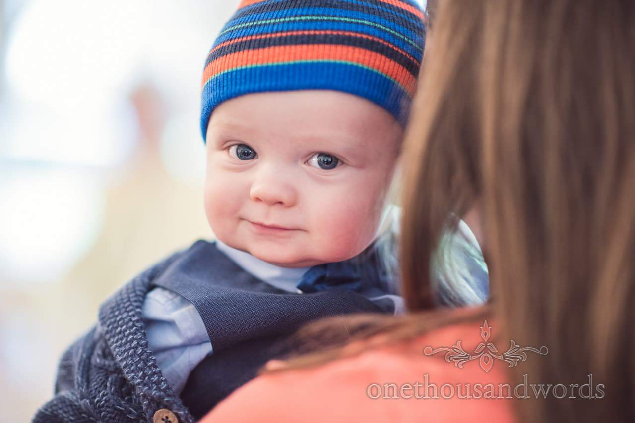 Baby wedding guest photograph with blue eyes and colourful stripey hat